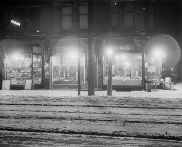 Exterior view of store fronts at 1498 Queen Street West, Parkdale, with Humphrey gas arc lighting: Sutherland tobacco, A. Grapple shoes, F. G. Martin, grocer. - [ca. 1922]